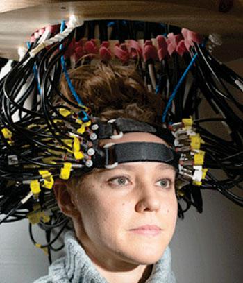 Imagen A: Britt Gott, participante en la investigación, porta una gorra utilizada para obtener imágenes del cerebro mediante tomografía de difusión óptica (DOT) (Fotografía cortesía de la Facultad de Medicina de la Universidad de Washington en St Louis).